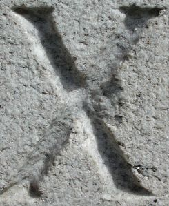 The letter x carved in stone
